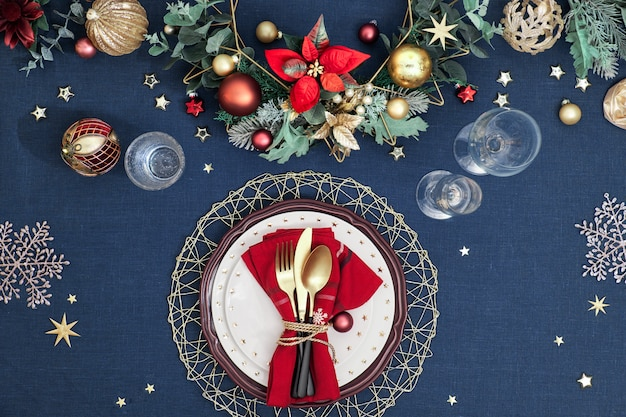 Christmas table setup with dark red white plates, red paper ring and poinsettia, golden utensils. red, green and golden gilded decorations. flat lay. Premium Photo