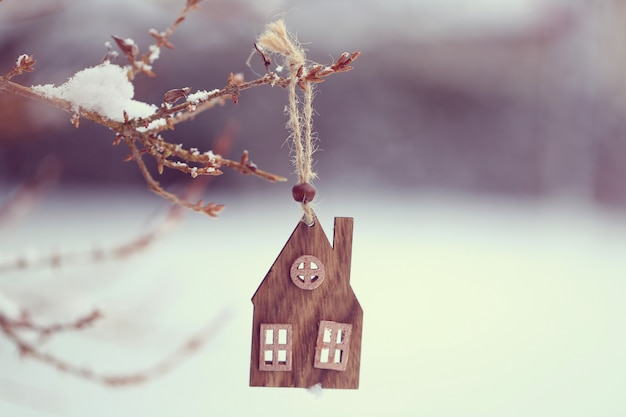 Christmas time. wooden small house on a branch in winter and snow Premium Photo