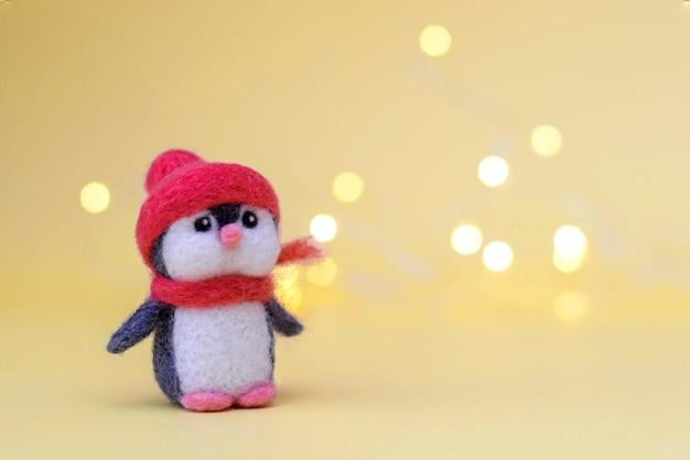 Елочная игрушка из валяной шерсти милый маленький пингвин в зимней красной шапке и шарфе на желтом фоне с боке, копией пространства Premium Фотографии