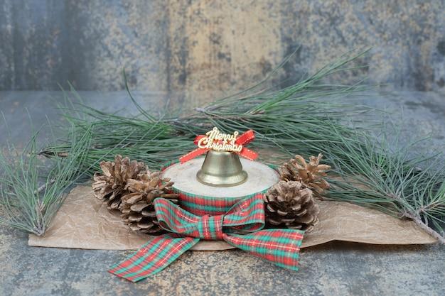 大理石の背景に弓と2つの松ぼっくりのクリスマスのおもちゃ。高品質の写真 無料写真