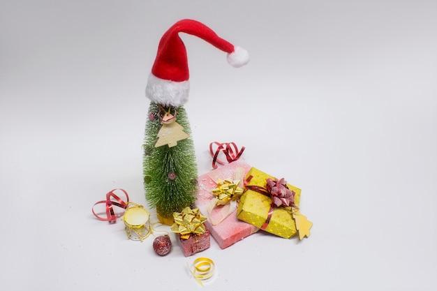 Рождественская елка и украшения с праздничной светящейся лампой, подарками и яркими бантами на белом фоне. рождественские и новогодние композиции. Premium Фотографии