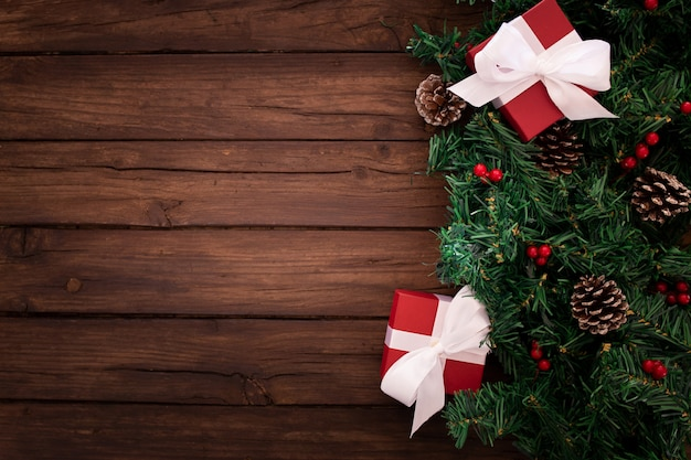 Christmas tree branch with gifts on a wooden background Free Photo