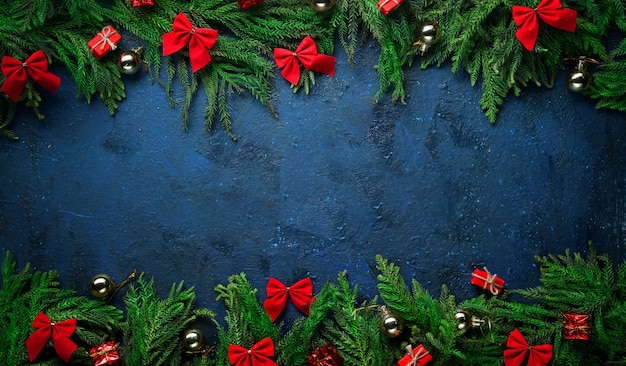 Christmas tree branches and decoration on top and bottom. banner dark blue background copy space. Premium Photo