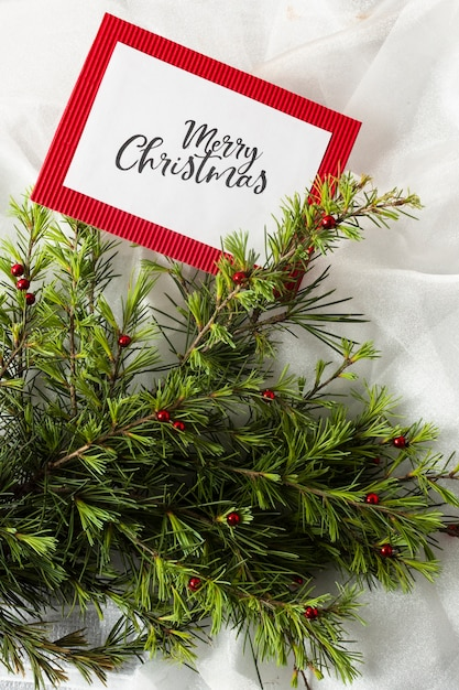 Christmas tree branches on white cloth with christmas card mock-upm Free Photo