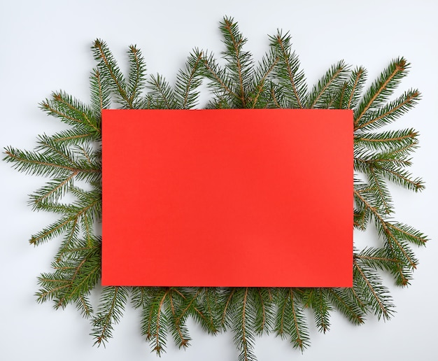 Christmas tree branches with an empty red sheet Premium Photo