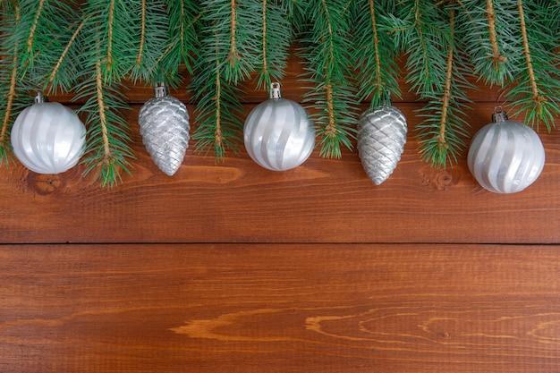 Елочные ветви с новогодними игрушками на деревянных фоне Premium Фотографии