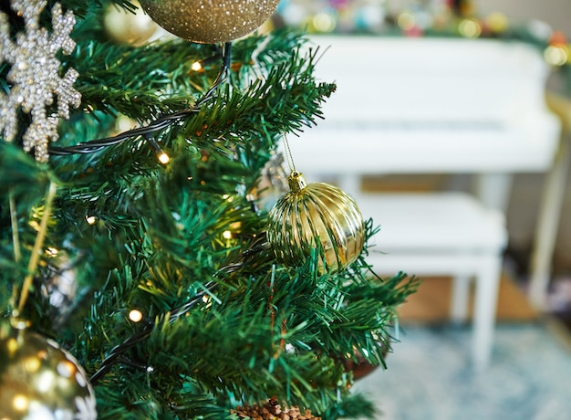 Christmas tree decorated with toys. against the surface of a white grand piano Premium Photo