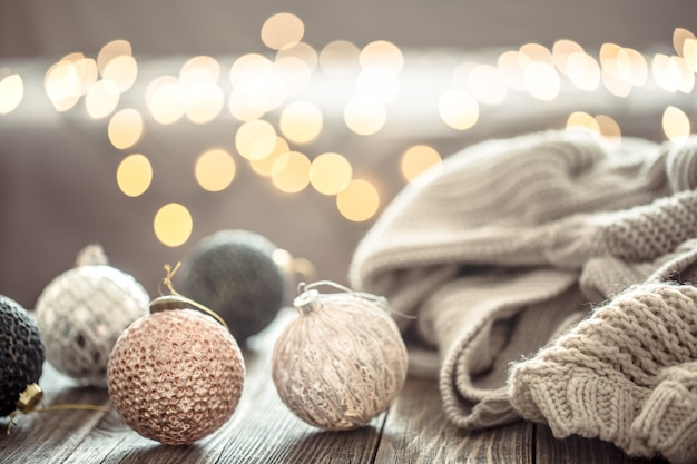 Christmas tree decorations over christmas lights bokeh in home on wooden table with sweater on a wall and decorations. Free Photo