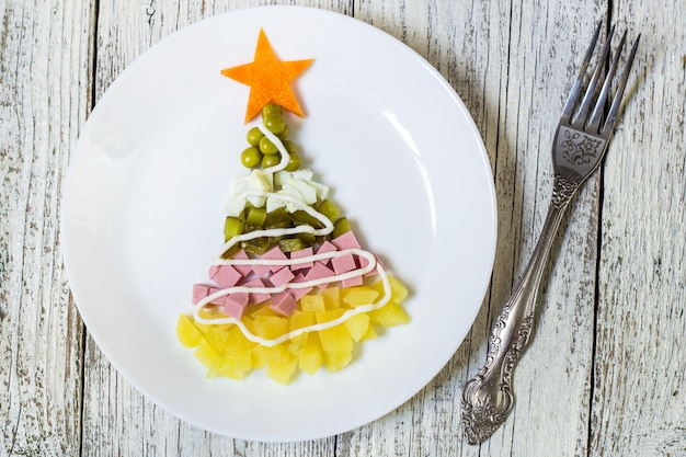 Christmas tree fromsalad olivier in plate on a white wooden table. top view Premium Photo
