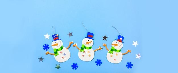 飾りをぶら下げてクリスマスツリー。青い背景に雪だるまのパーツ。 Premium写真