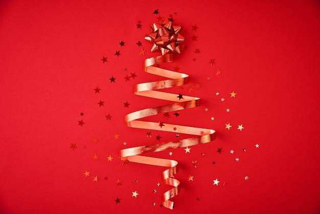 축제 리본 및 빨간색 배경에 색종이에서 만든 크리스마스 트리. 크리스마스 장식 프리미엄 사진