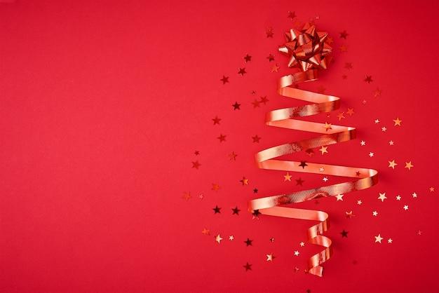 お祝いのリボンと紙吹雪から作られたクリスマスツリー Premium写真