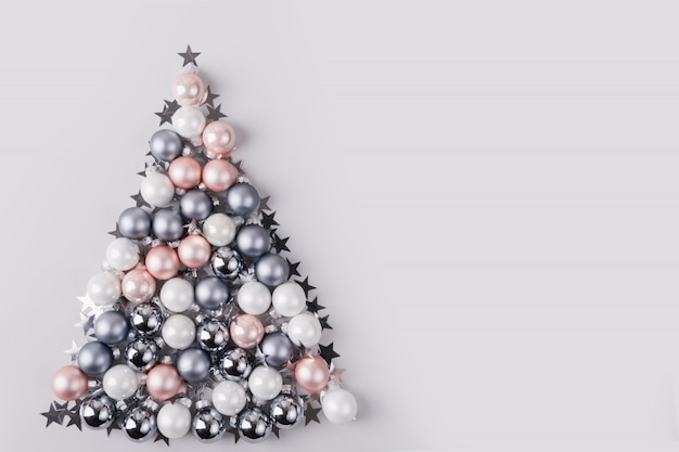 Christmas tree made of stars, silver balls on grey background. xmas composition. flat lay, top view, copy space. holiday greeting card. Premium Photo