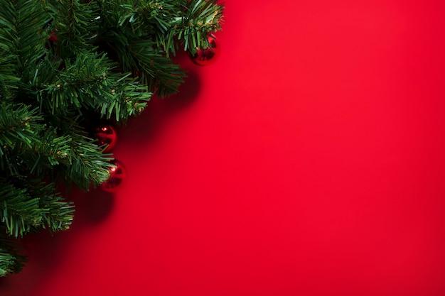 Рождественская елка на красном фоне с копией пространства Premium Фотографии