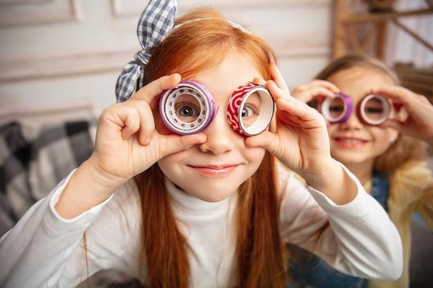 Рождественская елка. двое маленьких детей, девочки вместе в творчестве. счастливые малыши делают игрушки ручной работы для игр или празднования нового года. маленькие кавказские модели. счастливое детство, подготовка к празднику. Бесплатные Фотографии