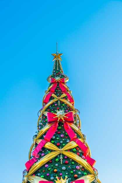 Christmas Tree With Big Bows On A Blue Background In Vertical Free Photo