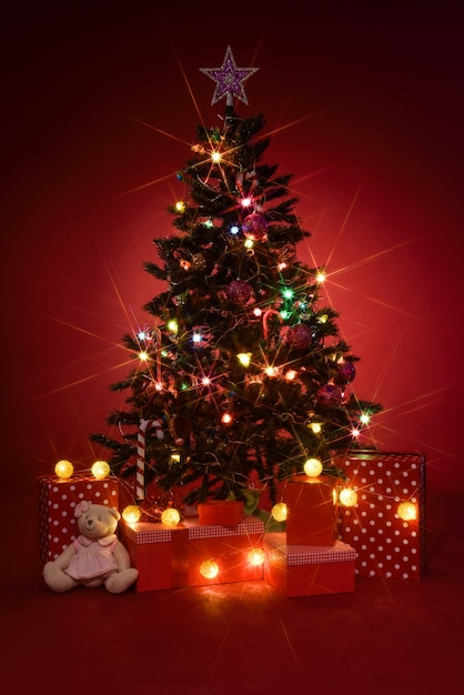 Christmas tree with gifts on red background Free Photo