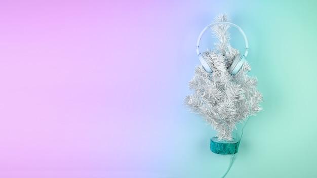 Christmas tree with headphones on pastel pink blue background Premium Photo