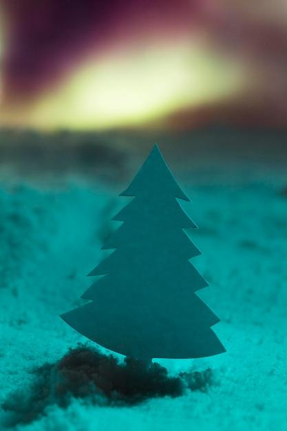 Christmas tree with snow and aurore borealis Free Photo