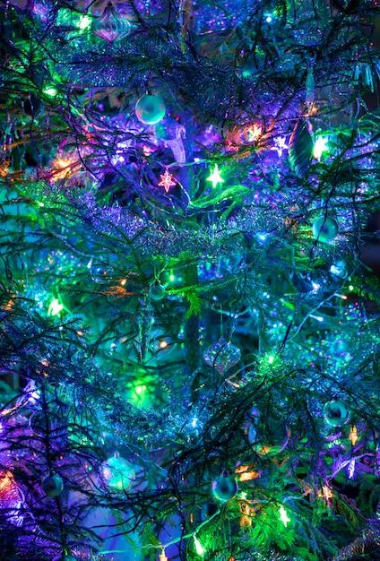 おもちゃ、花輪、紫、青、緑の色の見掛け倒しのクリスマスツリー。背景や壁紙として飾られたクリスマスツリーの一部。垂直方向。ソフトフォーカス。 Premium写真