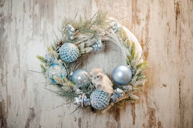 Christmas white artificial wreath with light blue decoration and little toy owl Premium Photo