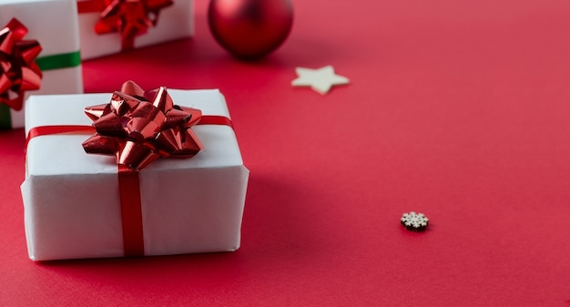 Christmas white handmade gift boxes on a red background tied with a red ribbon and gingerbread cookies Premium Photo