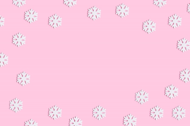 Christmas or winter composition of snowflakes on pastel pink background. Premium Photo