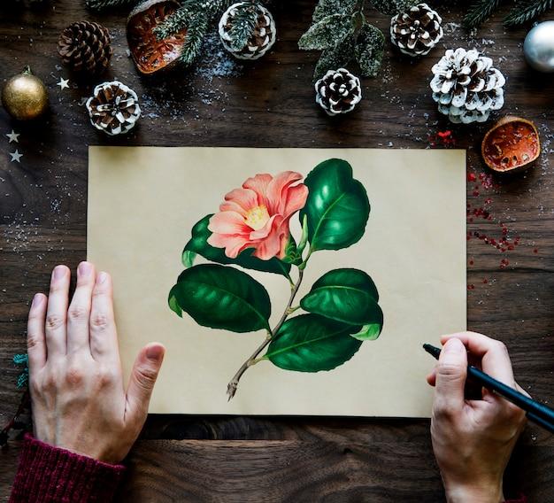 松ぼっくりと花の絵が描かれたクリスマスの願いカード 無料写真