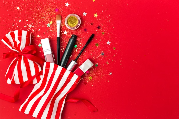 Christmas  with mascara, lipstick and shadows. flat lay composition with sparkles, gift bags and cosmetic products for the new year party. Premium Photo