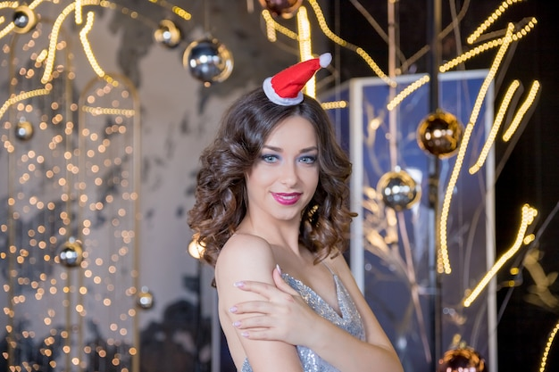 Christmas woman. beauty model girl in santa claus hat with red lips and manicure looking to camera with a surprised expression. closeup portrait. emotions. enjoying new year sale, winter holidays Premium Photo