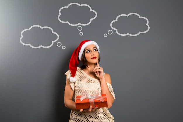 크리스마스 여자 찾고 빈 복사본 공간 보류 선물 상자 선물, 젊은 행복 미소 여자 산타 클로스 모자, 매력적인 새해 파티 소녀, 빈 풍선과 함께 칠판 위에 착용 프리미엄 사진