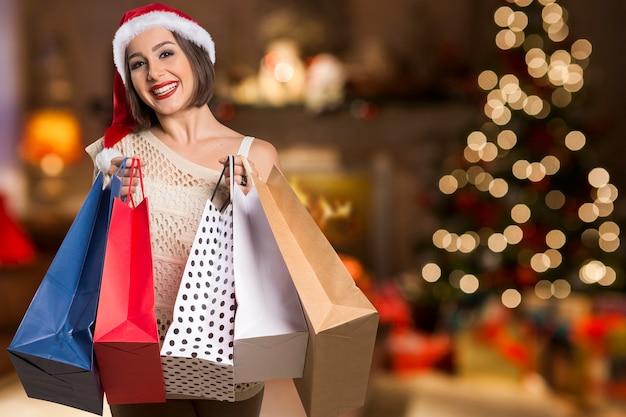크리스마스 여자 초상화 개최 쇼핑 가방. Bokeh 크리스마스 불빛에 웃는 행복 한 여자 프리미엄 사진
