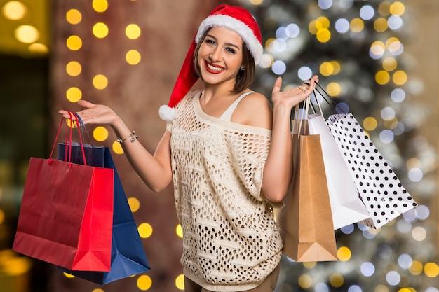 크리스마스 선물을 들고 크리스마스 여자 초상화입니다. Bokeh 크리스마스 불빛에 웃는 행복 한 여자 프리미엄 사진