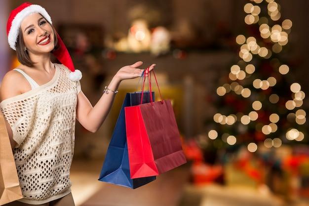 크리스마스 여자 초상화 쇼핑 가방을 들고입니다. Bokeh 크리스마스 불빛에 웃는 행복 한 여자 프리미엄 사진