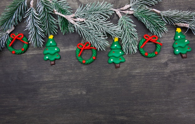 Christmas wooden background with christmas tree and red decorations. Premium Photo
