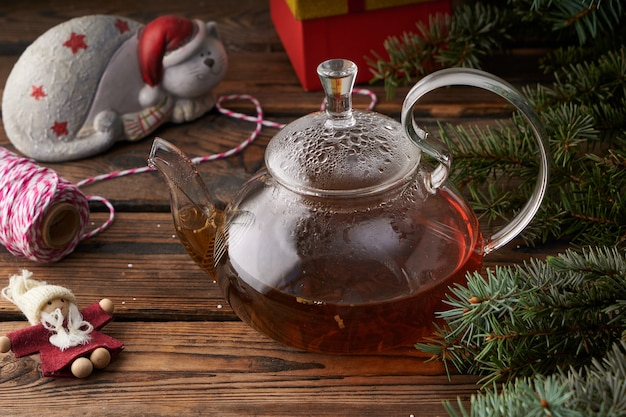 おもちゃ、装飾、ホットティーとモミの枝のティーポットとクリスマスの木製の背景。クリスマスのコンセプト Premium写真