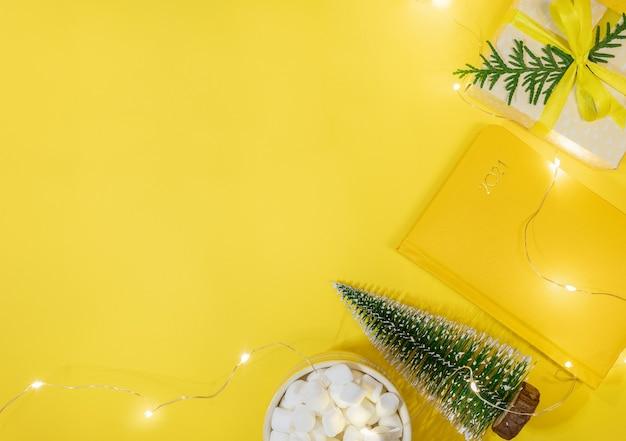 Рождественская концепция рабочего пространства в желтом цвете. рамка блокнота-органайзера на 2021 год, маленькая новогодняя елка, подарочная коробка своими руками, чашка какао с зефиром, рождественские огни. планирование. вид сверху, плоская планировка. скопируйте пространство. Premium Фотографии