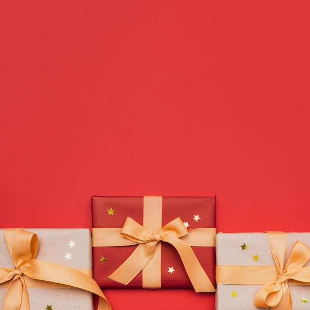 Christmas wrapped gift with stars on red background Free Photo