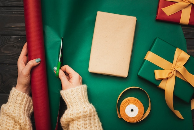 Christmas wrapping paper being cut for present Free Photo