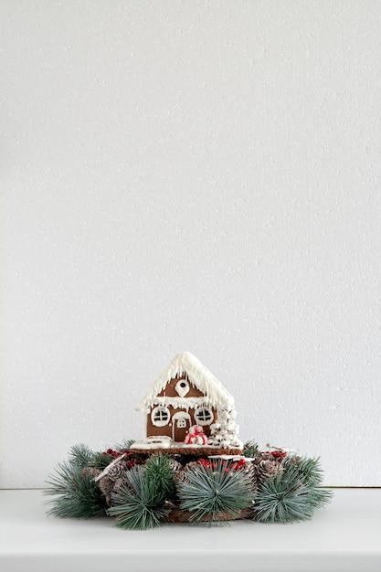 白い背景の上のクリスマスリースとジンジャーブレッドハウス。大晦日とクリスマス。スペースをコピーします。 Premium写真