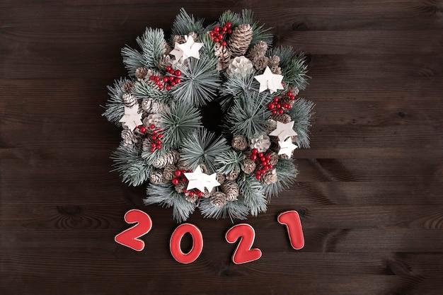 クリスマスリースと木製の背景に碑文2021ジンジャーブレッドクッキー。 Premium写真