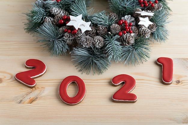 ジンジャーブレッドのクリスマスリースと赤い番号2021。メリークリスマスの背景。 Premium写真