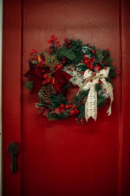 Christmas wreath hanging on red door Premium Photo