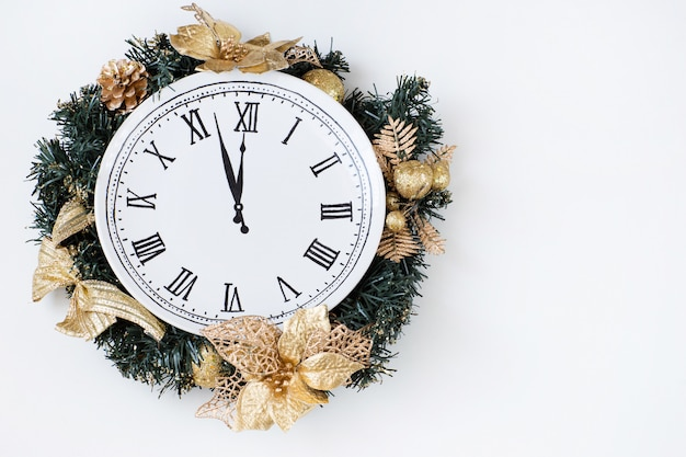 Premium Photo | Christmas wreath made of fir branches, golden toys and  inside the clock, happy new year