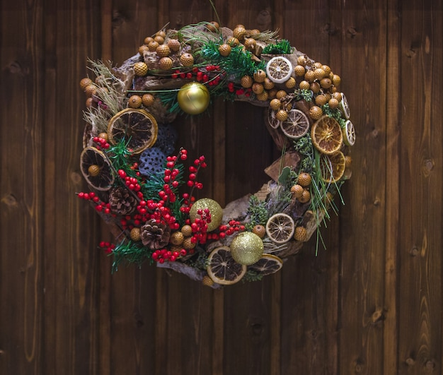 Christmas wreath with holly berry and dry orange slice hanged on the door Free Photo