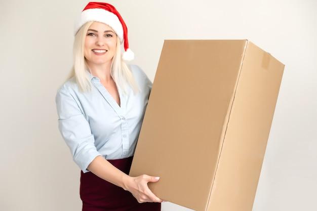 Рождество, рождество, зима, концепция счастья - улыбающаяся женщина в шляпе санта-помощника с коробкой для посылок Premium Фотографии