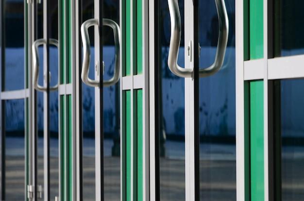 Chrome door handle and glass of modern aluminium office facade Premium Photo