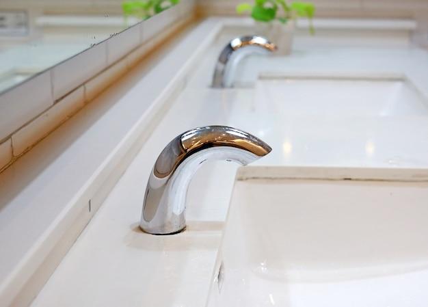 Chrome minimalist tap in restroom. Premium Photo