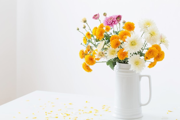 背景の白い壁に白い水差しの菊の花 Premium写真