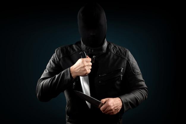 シリアルキラー、彼の頭の上にナイフと黒いchuolkomを持つマニアック Premium写真
